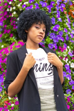 Street style, girl with afro hair in some city flowers
