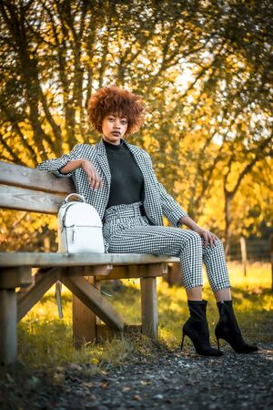 A smiling young Dominican woman sitting on a bench in autumn Stock Photo
