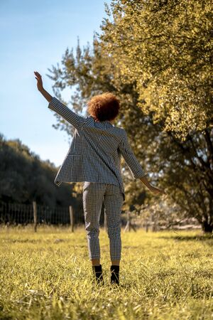 Lifestyle session of a young Dominican woman with arms raised dancing in autumn