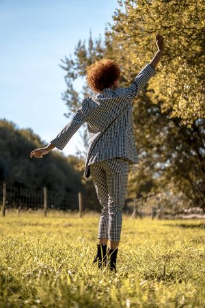 Lifestyle session of a young Dominican woman with a raised arms dancing in autumn