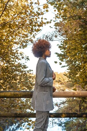 A Dominican girl with afro-red hair in an autumn session, in a beautiful plaid suit