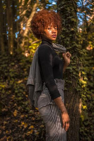 Lifestyle session of a Dominican models in nature in autumn, looking at the ground