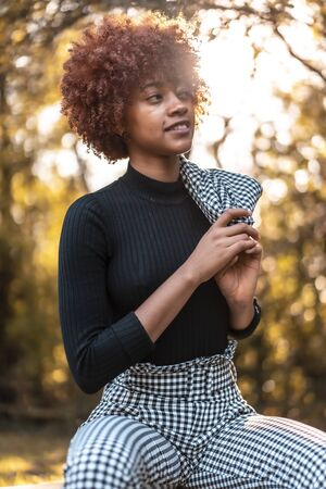 Cheerful afro-haired model photographed inside sitting in a beautiful plaid suit