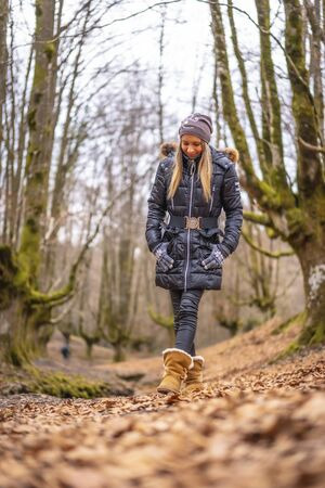 Lifestyle, a pensive young blonde woman walking through an enchanted forest