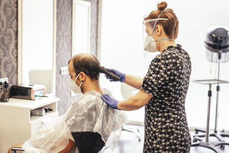 Hairdresser with security measures for the covid-19, new normality, social distance, hairdresser cutting hair with mask and protective plastic screen