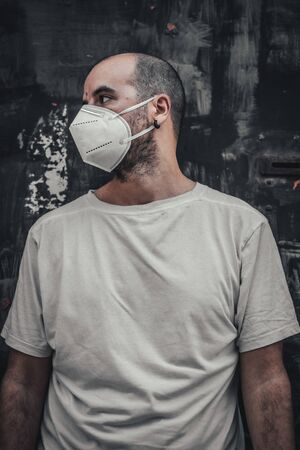 A young man in a white shirt and mask at a black metal door with a scab. Health emergency, pandemic Covid-19