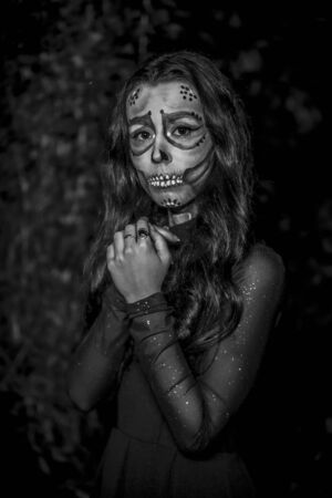 Halloween session, portrait of a scared young woman dressed as a Mexican skull with flowers on her head, in black and white