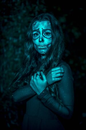 Halloween session, portrait of a scared young woman dressed as a Mexican skull with flowers on her head, with blue light Stock Photo