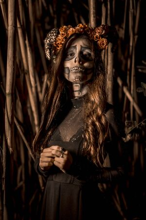 Halloween session, Mexican skull with flowers on the head, a young woman disguised in a forest with sepia color Stock Photo