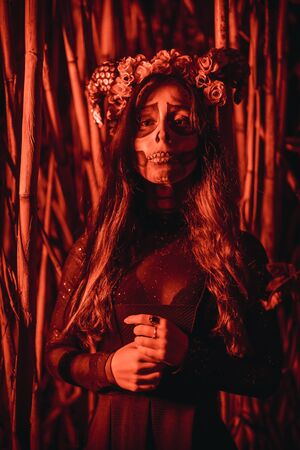 Halloween session, Mexican skull with flowers on the head, a young woman disguised in a bamboo forest with red light Stock Photo
