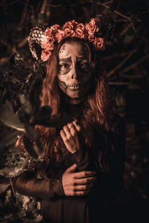 Halloween, Mexican skull with flowers on the head, a young woman in disguise