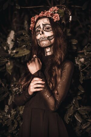 Halloween, a young woman dressed as a Mexican skull with flowers on her head. With lights last night in a forest