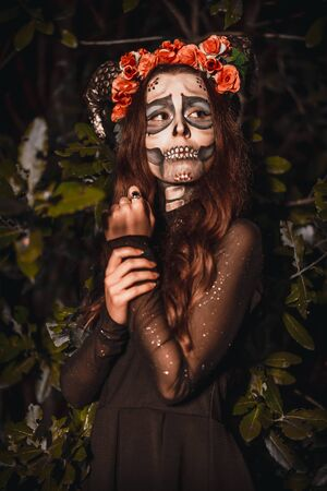 Halloween, a young woman dressed as a Mexican skull with flowers on her head. Photo with night lights in a forest