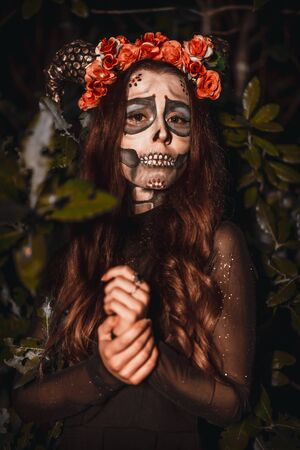 Halloween, a young woman dressed as a Mexican skull with flowers on her head. Photo with night lights Stock Photo