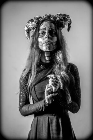 Halloween, a young woman dressed as a Mexican skull with flowers on her head. Black and white photo