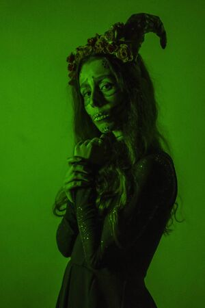 Halloween, a young woman dressed as a Mexican skull with flowers on her head. With green light Stock Photo