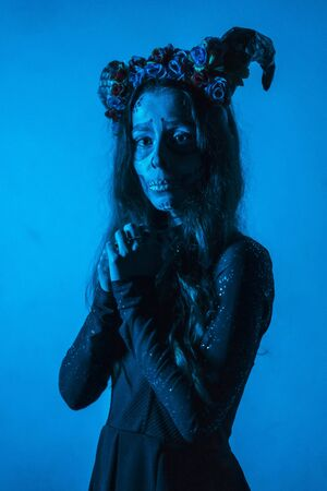 Halloween, a young woman dressed as a Mexican skull with flowers on her head. With blue light