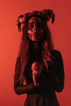 Halloween, a young woman dressed as a Mexican skull with flowers on her head. With red lighting Stock Photo