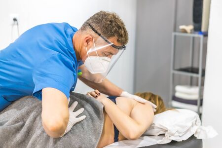 Physiotherapist with screen and mask giving a hip massage to a young woman. Reopening with physiotherapy safety measures Stockfoto