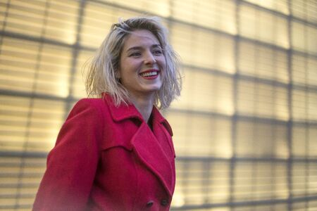 A pretty smiling young blonde woman at night wearing a red blazer, street style
