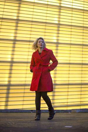 A pretty young blonde woman strolling in a red blazer, street style