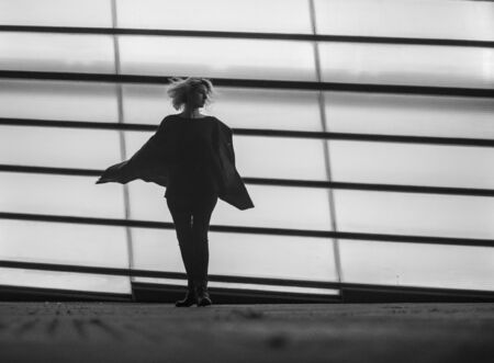 Silhouette of a young girl dancing in the city, black and white photo