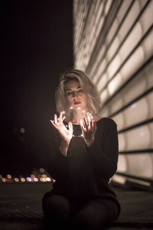 Street Style. A young blonde woman with small lights in her hands
