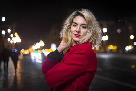 Lifestyle, a pretty blonde with a red blazer and city lights in the background in an urban session