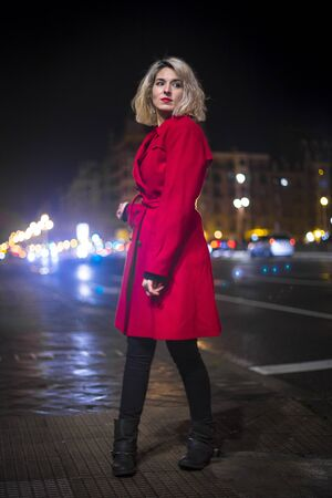 Lifestyle, a young blonde woman with a red blazer and city lights in the background in an urban session Reklamní fotografie
