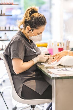 A young Latina worker at a manicure and pedicure salon with security measures and face masks. The reopening due to the covid-19 pandemic. Coronavirus Imagens