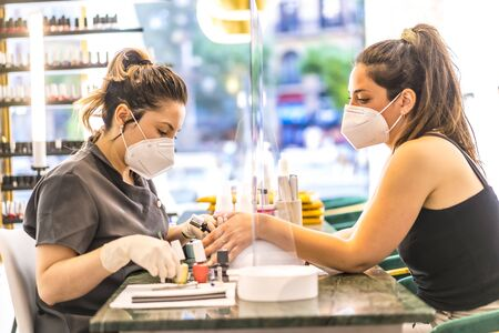 A worker with security measures and a face mask working with a client. Reopening after the coronavirus pandemic. Manicure and Pedicure Salon. Imagens