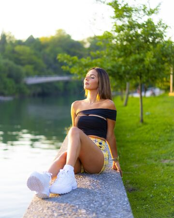 A young woman with her eyes closed imagining things. Sitting in a park by the river and trees. Brunette caucasian woman with tight black top, yellow skirt and white sneakers