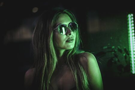 Caucasian brunette girl with sunglasses looking at a light green leds. Night urban photography