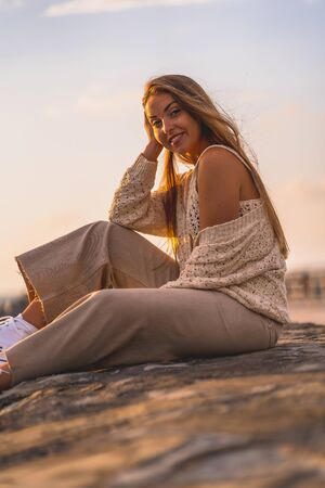 Summer lifestyle, portrait of a young blonde Caucasian woman sitting by the sea in a white short shirt and corduroy pants. Stock Photo