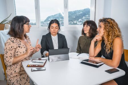 Young entrepreneurial session in the office, a young Latin American man and three young Caucasian women in a work meeting at the table