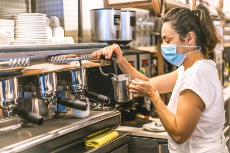 Photo session with a waitress with a face mask in a bar. New normality, security measures after the coronavirus pandemic, social distance, covid-19. Heating the milk in the machine to put a tea