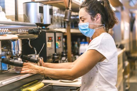 Photo session with a waitress with a face mask in a bar. New normality, security measures after the coronavirus pandemic, social distance, covid-19. Heating water in the machine to put a tea Stok Fotoğraf