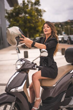 Lifestyle session on a motorcycle, a young blonde Caucasian businesswoman with a black blazer and white pants. About to put on the helmet Stok Fotoğraf