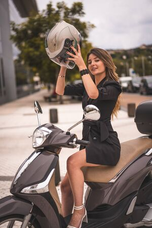 Lifestyle session on a motorcycle, a young blonde Caucasian businesswoman with a black blazer and white pants. Smiling about to put on the helmet