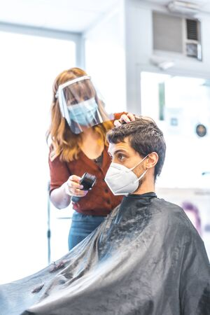 Hairdressing salon, coronavirus pandemic, covid-19. Security measures, face mask, protective screen, social distance. Working safely, cutting a young man's hair after quarantine with a razor