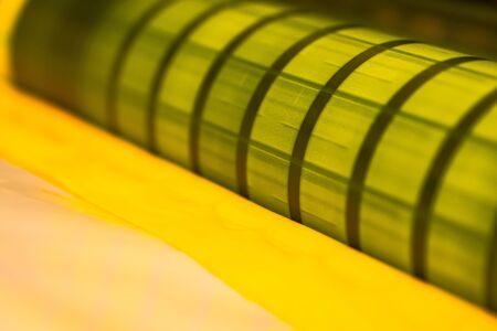 Traditional offset press. Printing in ink with CMYK, cyan, magenta, yellow and black. Graphic arts, offset printing. Detail of printing roller in offset machine of four bodies of yellow ink