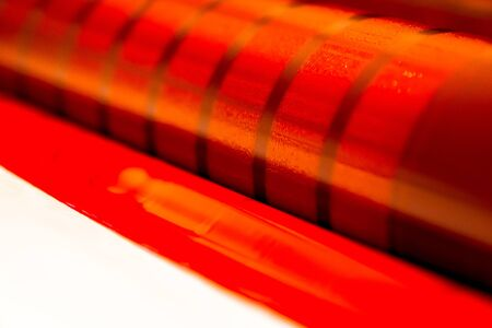 Traditional offset press. Printing in ink with CMYK, cyan, magenta, yellow and black. Graphic arts, offset printing. Detail of a printing roller in a four-body magenta offset machine Banque d'images