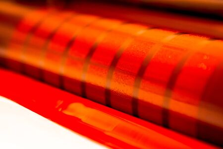 Traditional offset press. Printing in ink with CMYK, cyan, magenta, yellow and black. Graphic arts, offset printing. Detail of a printing roller in an offset machine with four bodies of magenta ink Banque d'images