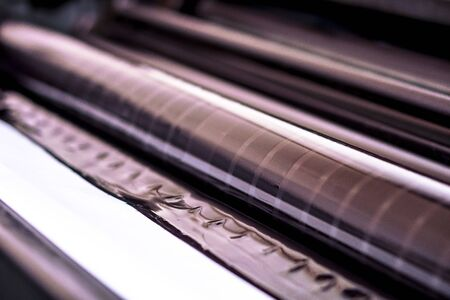 Traditional offset press. Printing in ink with CMYK, cyan, magenta, yellow and black. Graphic arts, offset printing. Detail of printing roller in offset machine of four bodies of black ink