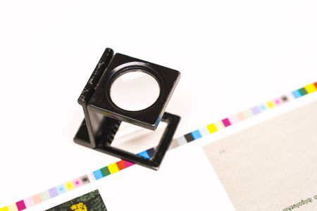 Photo session at an offset press. Printing in ink with CMYK, cyan, magenta, yellow and black. Graphic arts, offset printing. Thread counting adjustment tool