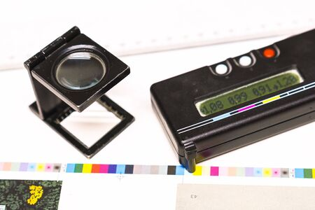 Photo session at an offset press. Printing in ink with CMYK, cyan, magenta, yellow and black. Graphic arts, offset printing. Measurement and adjustment tool, densitometer and thread counter Banque d'images