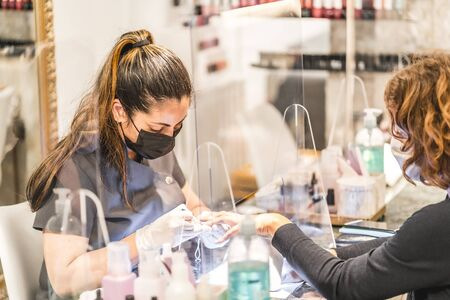 Manicure and pedicure salon, coronavirus, covid-19, social distance. The reopening due to the pandemic, security measures. Female worker with mask in nail salon