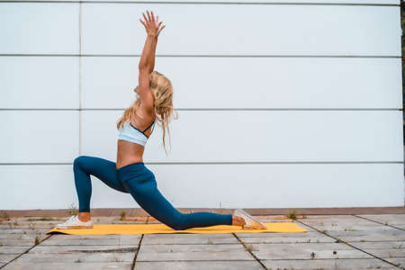 Yoga with blonde caucasian girl exercising on a yellow mat with a white wall in the background, with a blue maya on her legs and a white short shirt. Kneeling with arms up, profile posture