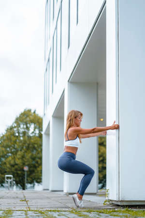 Fitness and yoga session with a young blonde Caucasian instructor dressed in a casual outfit. Exercising the knees bending down using a white column for support and standing on tiptoe