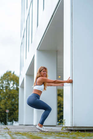 Fitness and yoga session with a young blonde Caucasian instructor dressed in a casual outfit. Exercising knees bending down using a white spine for support
